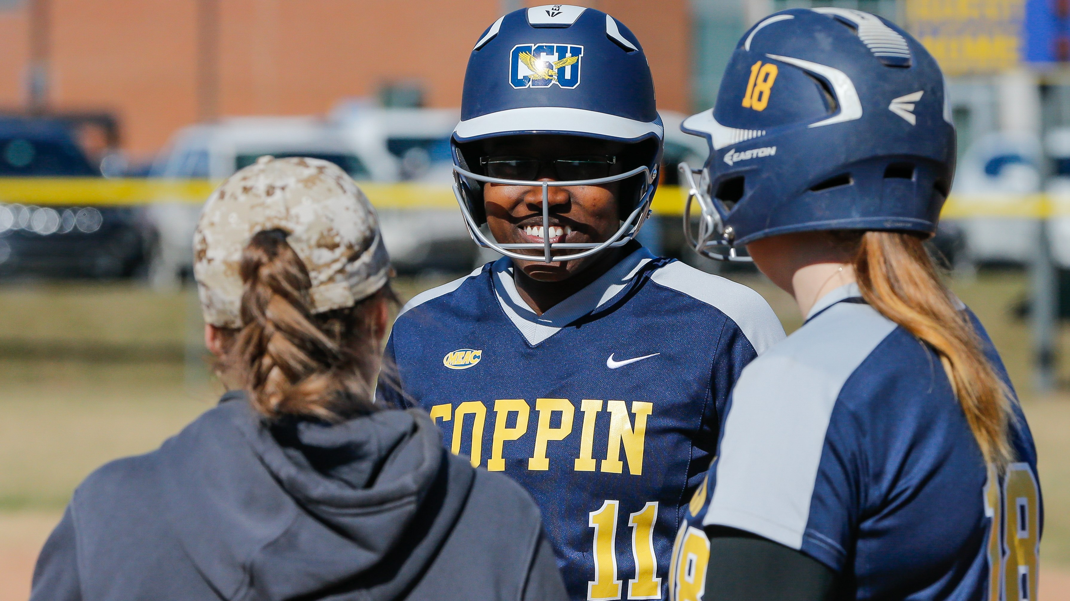 Nia Bowe chats with coach and teammate at 1st base